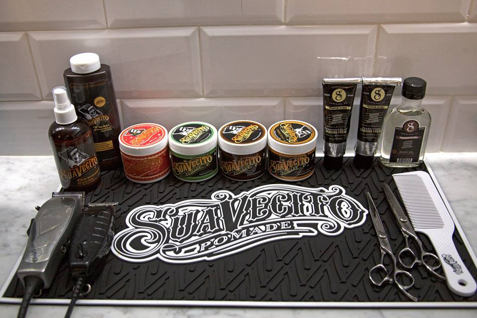 full range of suavecito barbering products on top of barber workstation mat