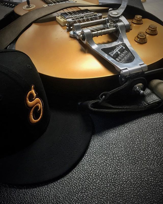 guitar with suavecito hat laying next to it