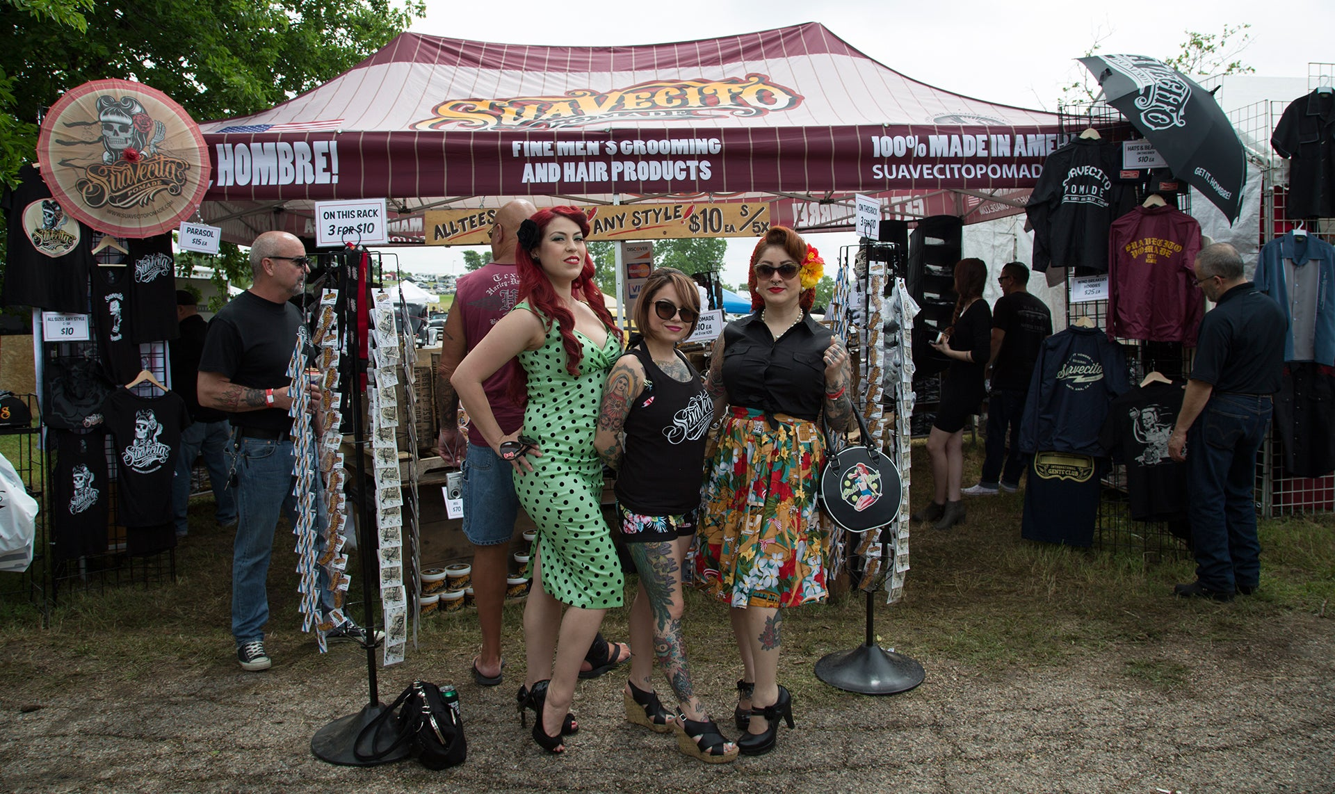 Three great looking girls posing in front of the Suavecito Pomade booth