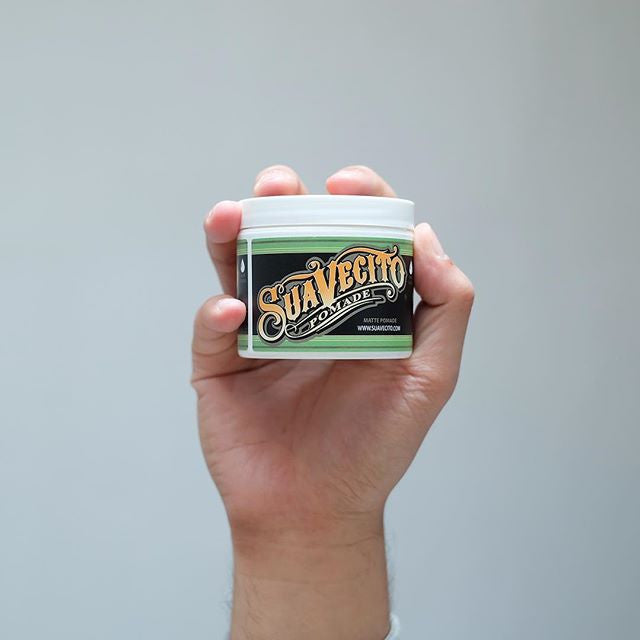 pomadebro holding can of matte pomade suavecito pomade