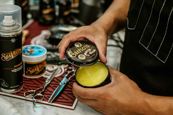 Barber openeing can of Suavecito Oil Based Pomade.