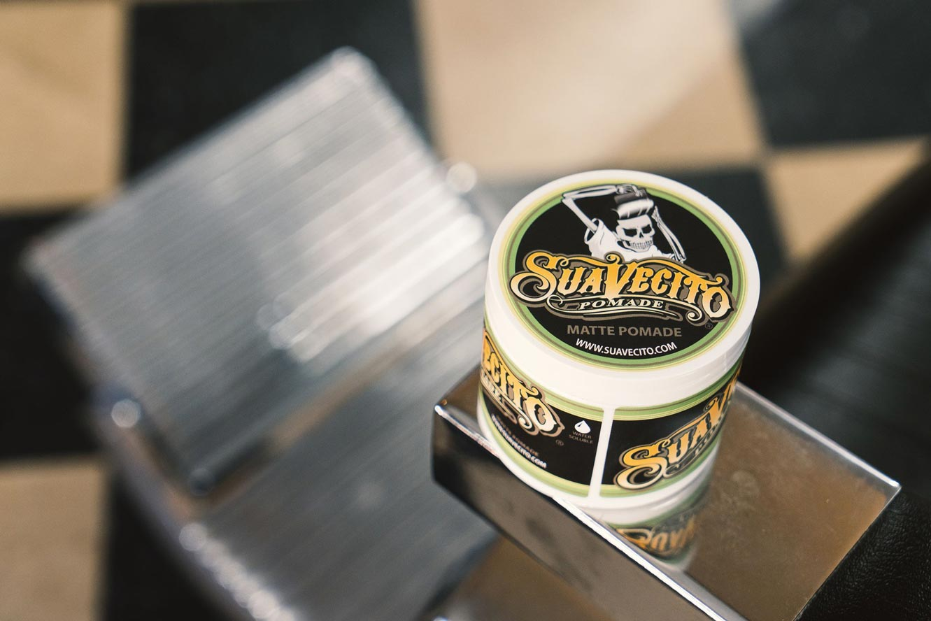 suavecito-matte-pomade-sitting-on-a-barbers-chair-in-barbershop