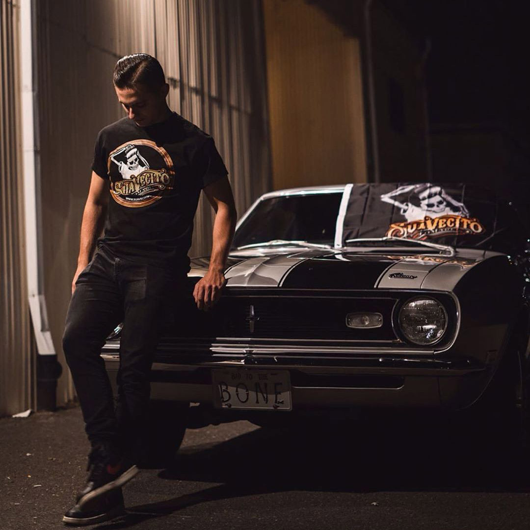 Man wearing a Suavecito OG Top Logo Shirt, leaning on a car
