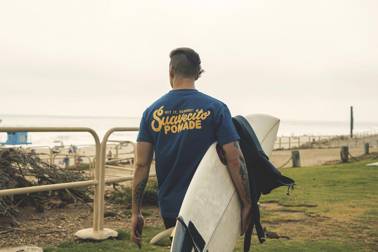 suavecito-wipeout-tee-worn-by-surfer-holding-surfboard-at-the-beach
