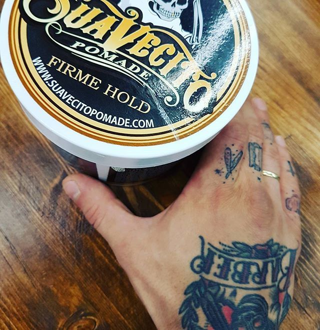 tub of suavecito pomade firme hold with tattooed hand