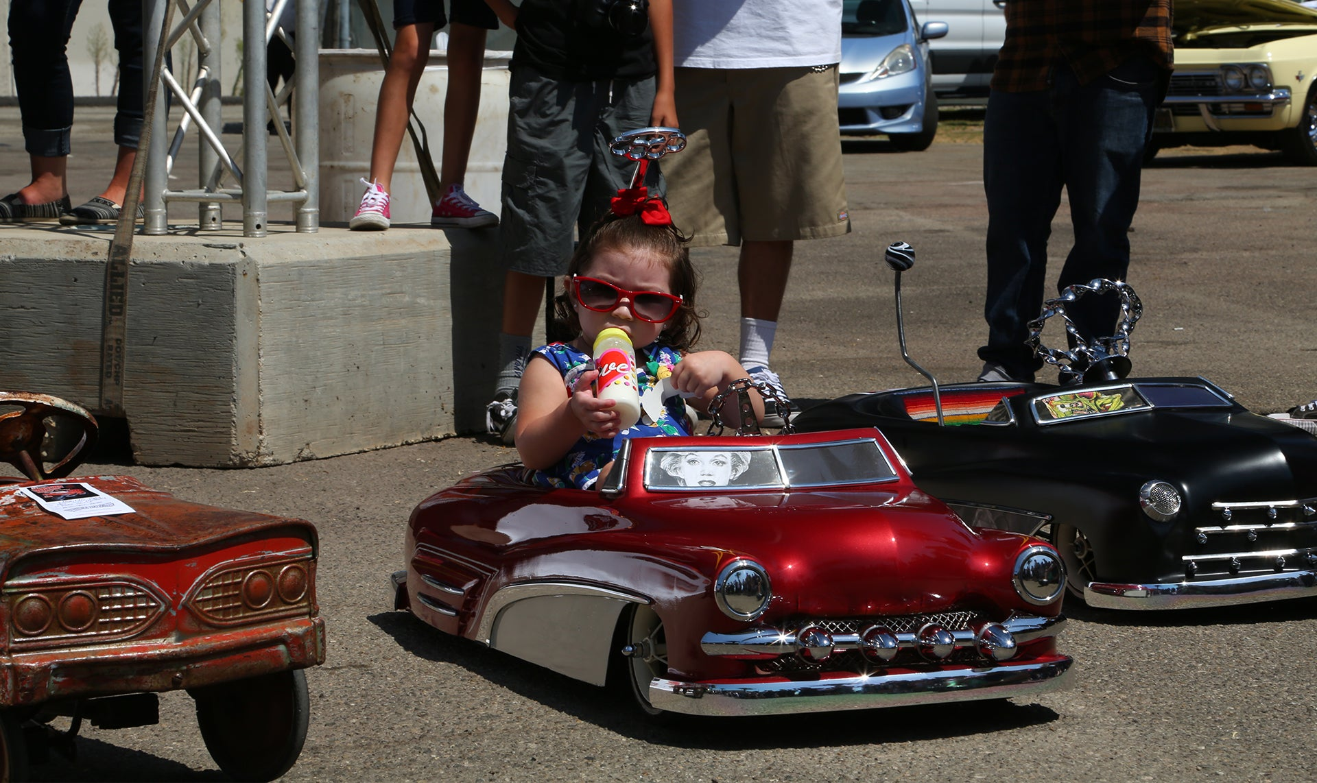 A lil lady enjoying the carshow in her toy car