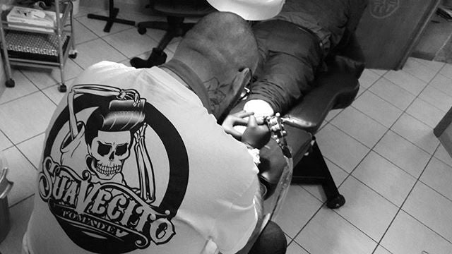 wearing a white suavecito t-shirt while tattooing leg