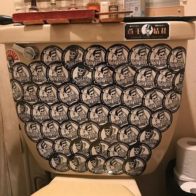 yuki_td_ a toilet covered in suavecito pomade stickers