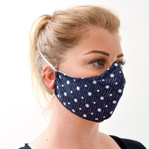 woman wearing a 3 layer reusable face mask with a dark blue and white shooting stars pattern sasmask by screen and shield