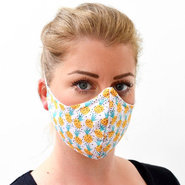 woman wearing a 3 layer reusable face mask with pineapples pattern sasmask by screen and shield