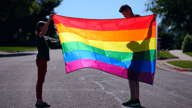 Pronouns Positive Step Forward. People Holding Gay Pride Flag.