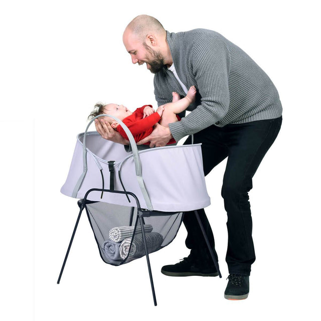 phil&teds carrycot stand with storage basket and nest baby bassinet on top and father taking baby out of bassinet 3/4 view_black