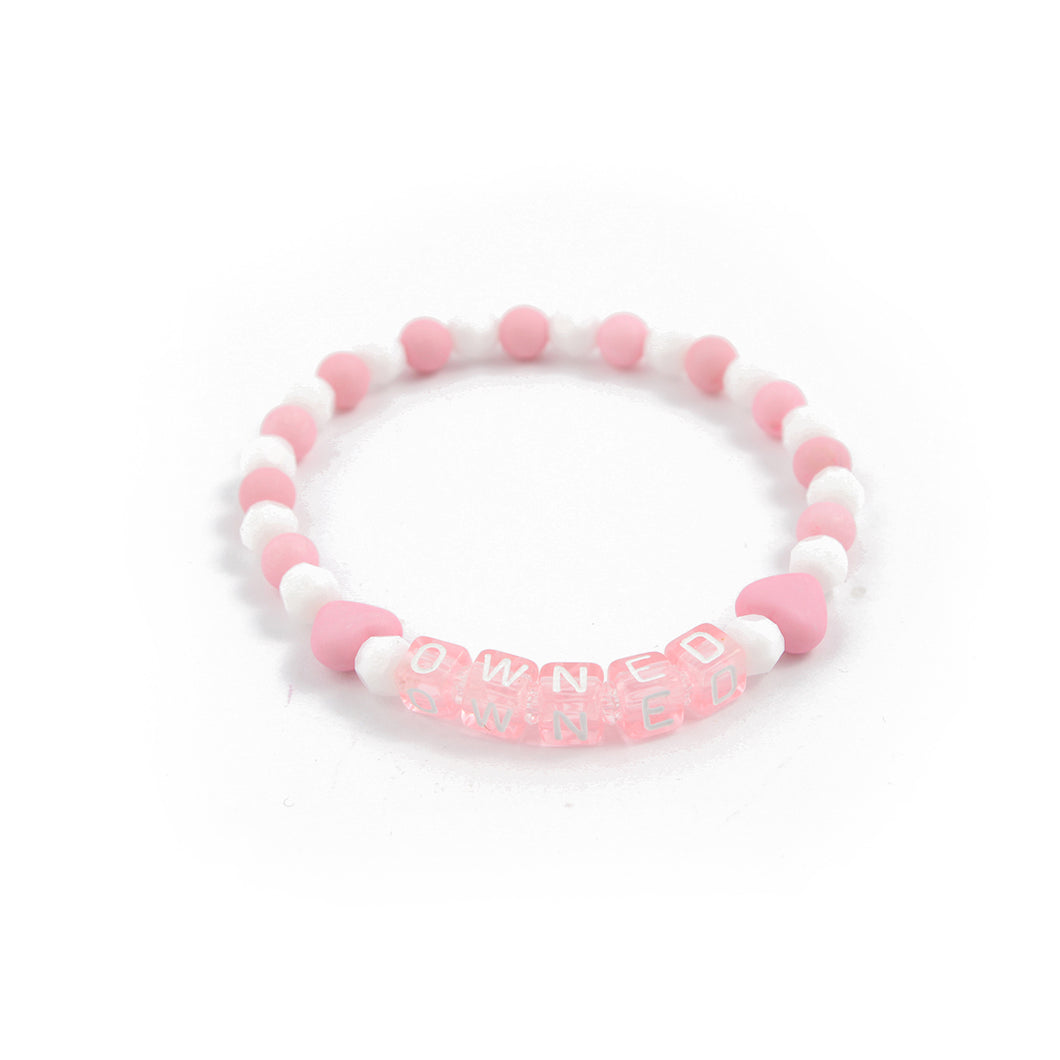 BDSM jewellery for submissives. Pink Hand made fetish bracelet saying OWNED. Perfect for DDLG abdl pet play submissives. Discreet ownership