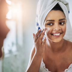 Young woman looking in mirror applying skincare