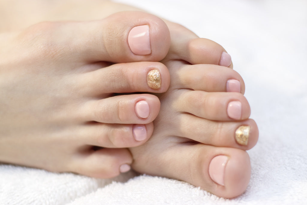 Soft feet resting on a white towel, with pink and gold nail polish