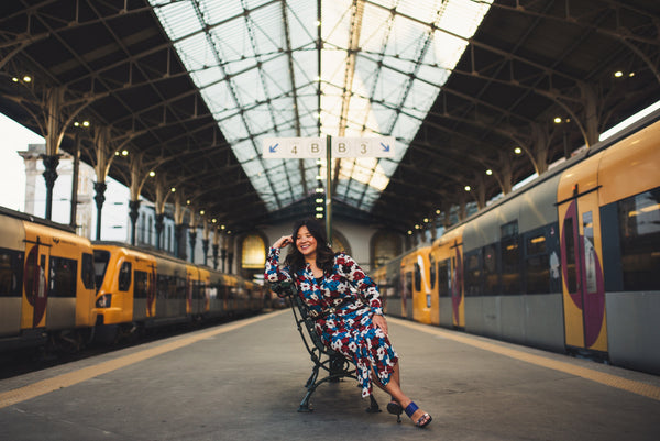 This is a photo of our founder, MJ Pham, sitting on a bench at a train station in Porto, Portugal, smiling and looking very happy as she considers how to make new creative tea blends inspired by desires and on ancient cultures.
