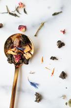 Load image into Gallery viewer, This is a gold spoonful of our Morning Sex tea blend set against a marble countertop with loose leaf tea pieces sprinkled like confetti all around.