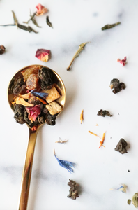 This is a gold spoonful of our Morning Sex tea blend set against a marble countertop with loose leaf tea pieces sprinkled like confetti all around.