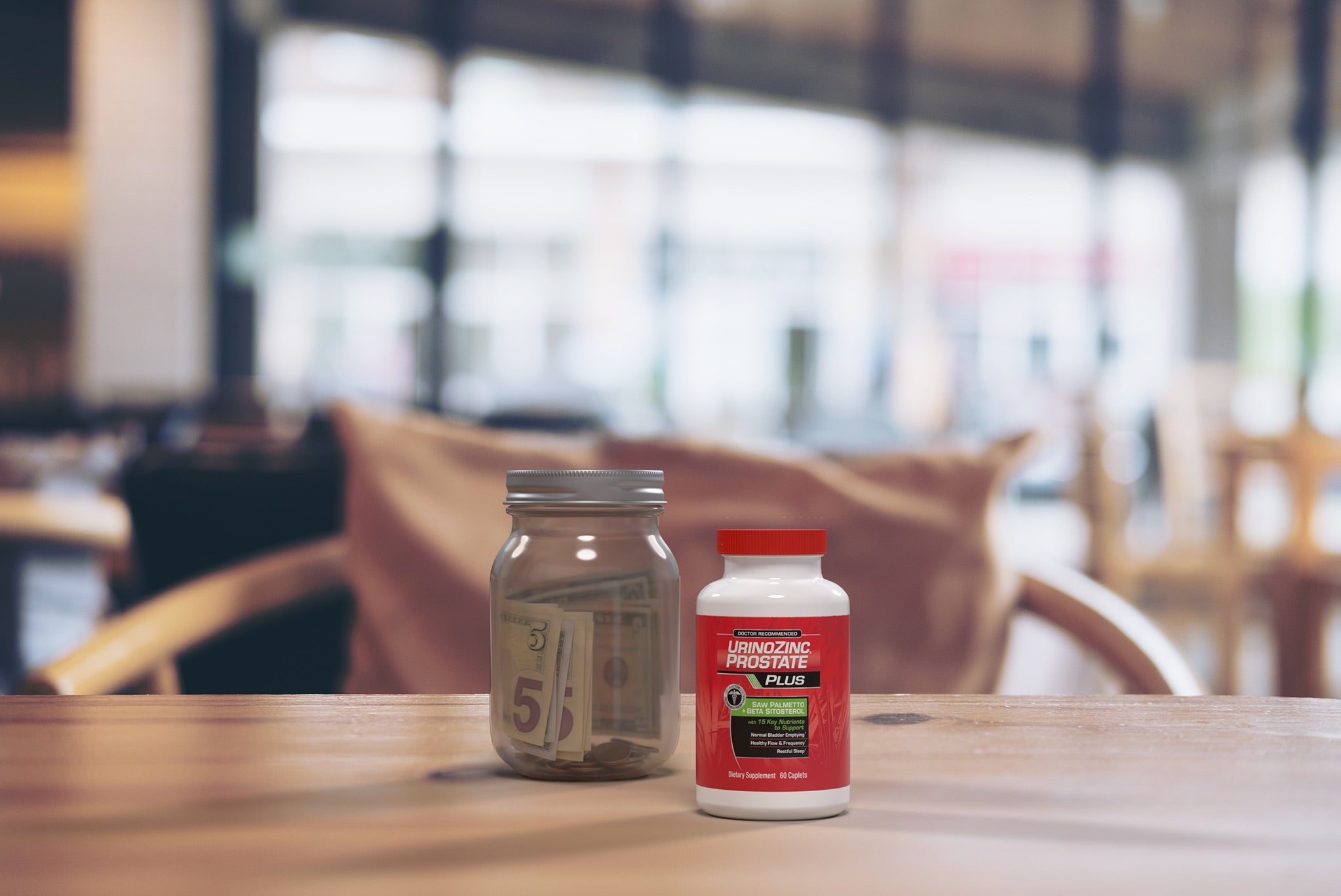 a photo of a bottle of UrinoZinc Plus sitting on a table next to a glass jar that contains money