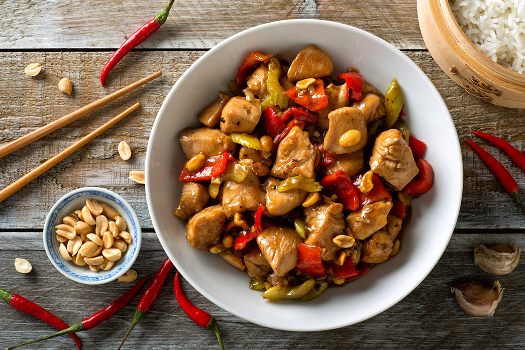 Kung Pao chicken in a white bowl with chopsticks and a bowl of peanuts