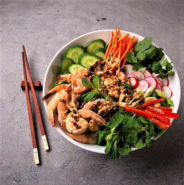 White shallow bowl with Chinese shrimp salad: Cucumbers, radishes, carrots, peppers, shrimp and herbs, topped with oo'mämē Chinese dressing
