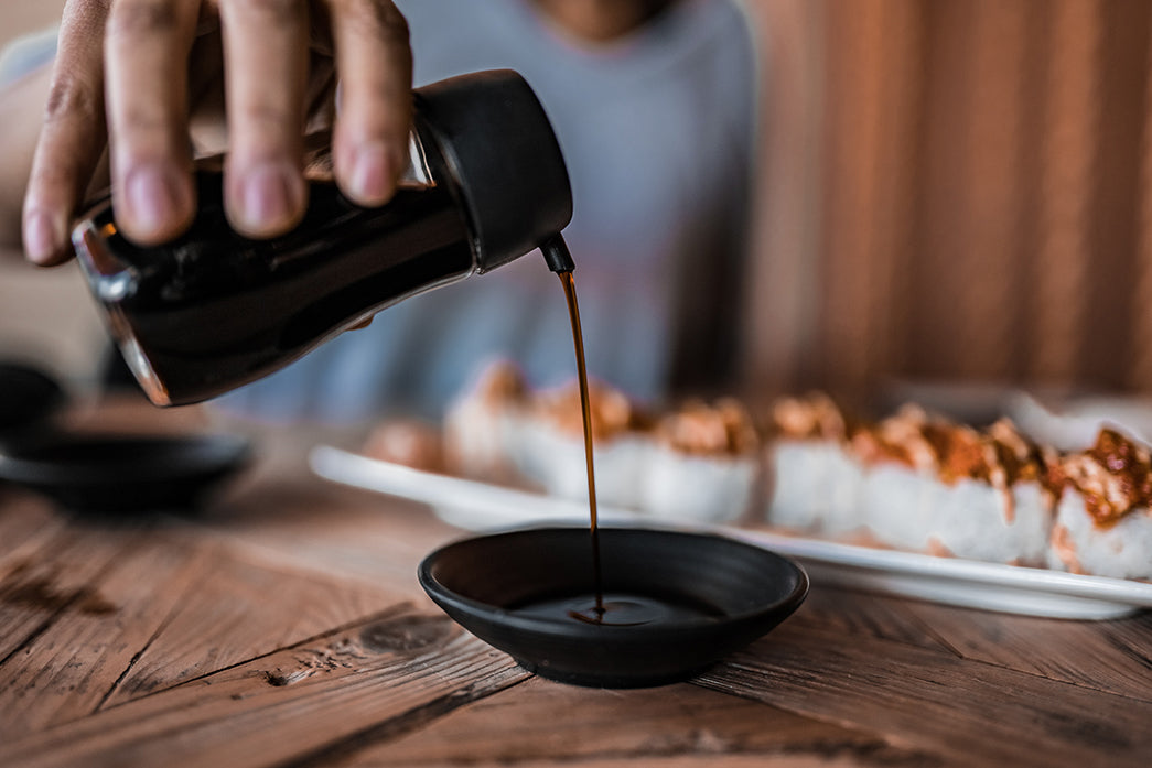 pouring soy sauce in a black saucer on bamboo mat #umami