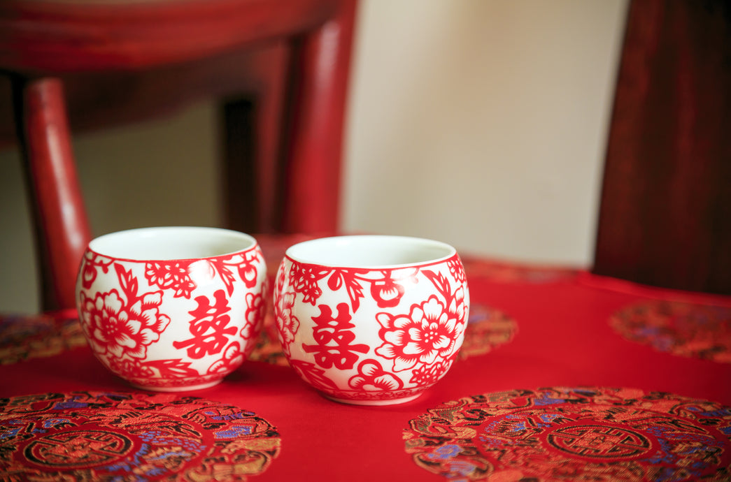 red tablecloth with two red and white cups, decorated with design and Chinese symbols for double happiness, with a red chair