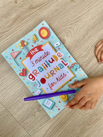 gratitude journal with pen and kids hand