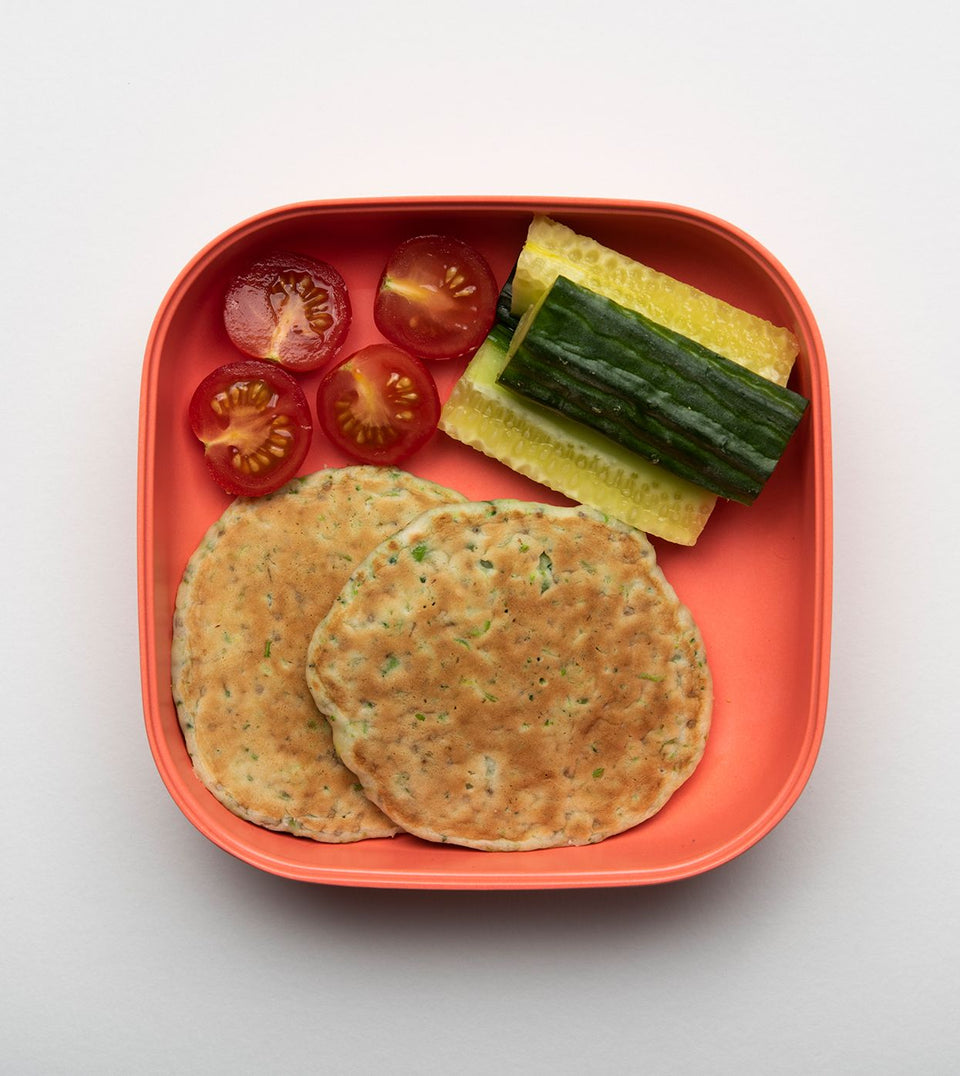 little senses whole foods broccoli and pea pancakes with chia seeds in red lunchbox with tomatoes and cucumber