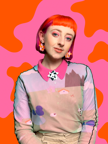 A portrait of Jess against a pink and orange cow print background. She is looking directly at the camera and smiling softly. She wears pink and red cosmic cow earrings and a black and white brooch. She has bright pink and orange hair.