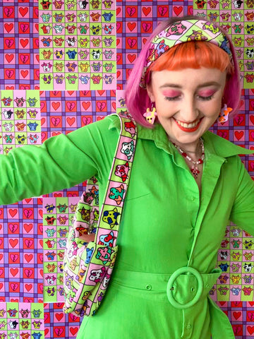 Jess is wearing a green jumpsuit and a cosmic cow printed bandana with a cosmic cow printed bag on her shoulder. She is looking down while smiling and her arms are spread wide.