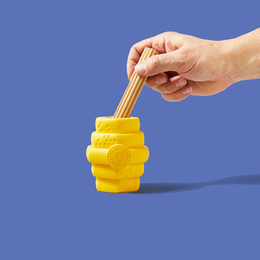 Two hands demonstrating how to insert a treat into the hollow cavity in the center of the Hive Chew Toy for Large Dogs