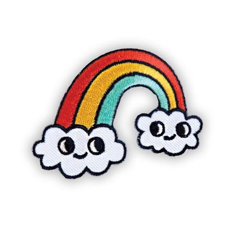 An embroidered fabric patch of a rainbow composed of three colours: red, gold, and light blue. Each end of the rainbow is capped by a smiling cloud.