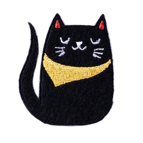 This embroidered patch is shaped like a cat. The cat is black with the face details embroidered in white. It is wearing a yellow bandana.