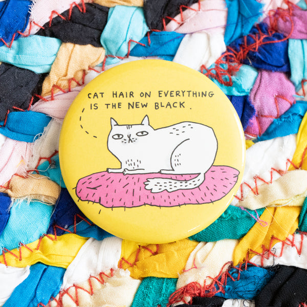 "A circular magnet. A disgruntled white cat sits on an unidentified pink object. The cat is saying ""cat hair on everything is the new black"". The background of the magnet is yellow."