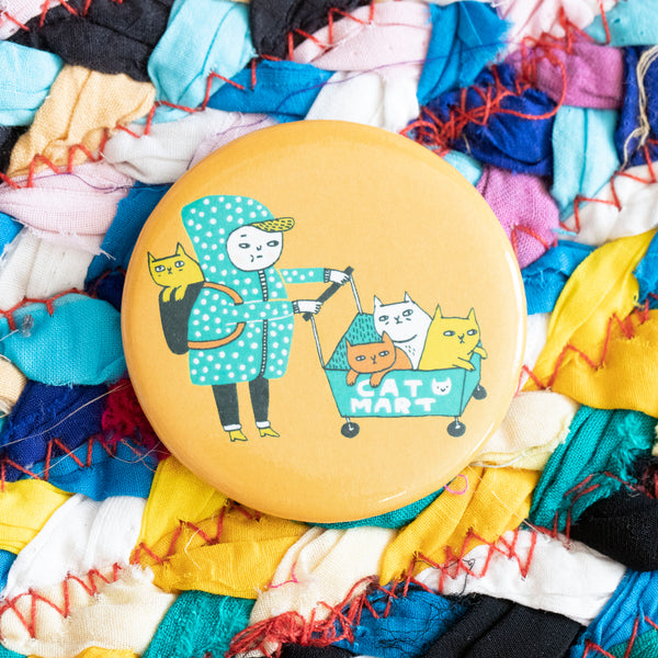 "A circular magnet. A disgruntled person pushes a shopping cart full of cats. There is a cat in their backpack as well. The cart says ""cat mart"". The person is wearing a blue polka dot hoodie with the hood up, and snazzy heeled boots. The background of the magnet is light orange."