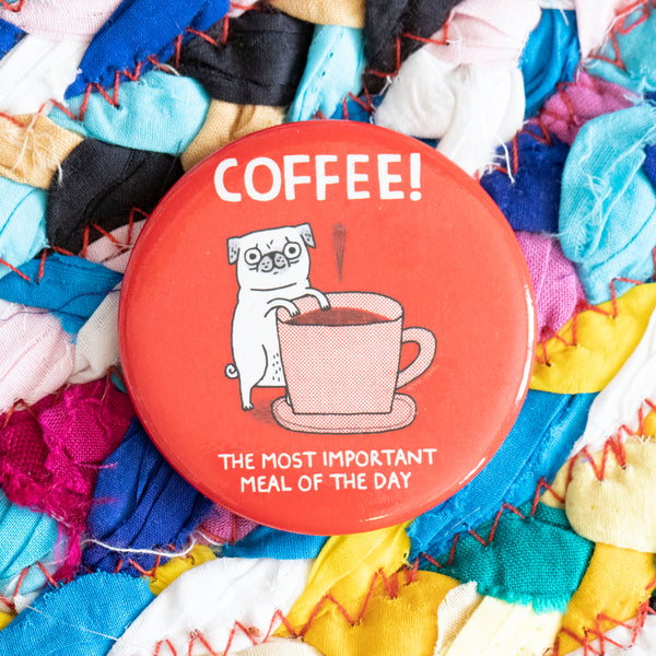 "A circular magnet. A white pug stands up against a pink and white plaid tea cup full of coffee. The magnet says ""Coffee! The most important meal of the day"".  The background of the magnet is red."