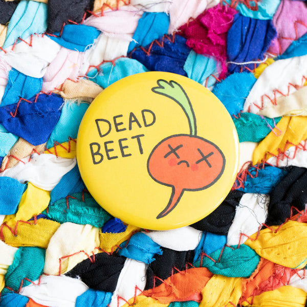 "A circular magnet. A dead beet features, with Xs for eyes and a frowny face. The words ""Dead beet"" are to the side. The magnet has a yellow background."