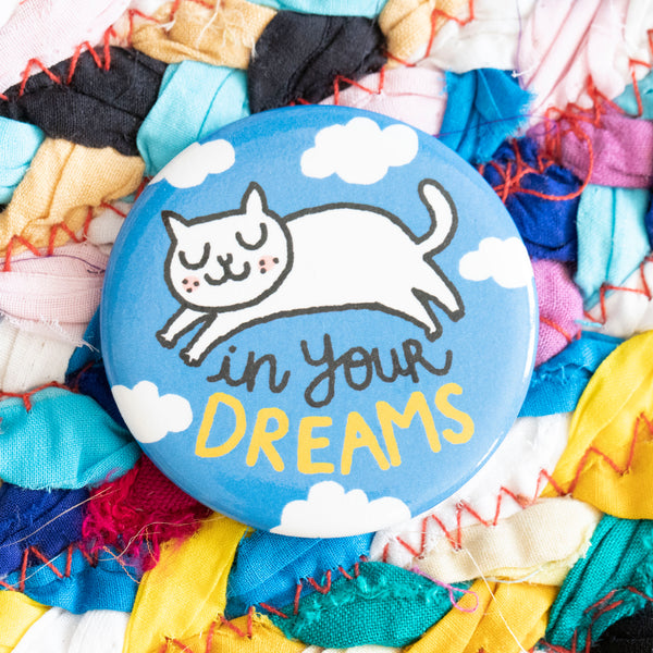 "A circular magnet. A white cat with their eyes closed stretches over the words ""in your dreams"". The background of the magnet is a blue sky with white clouds."