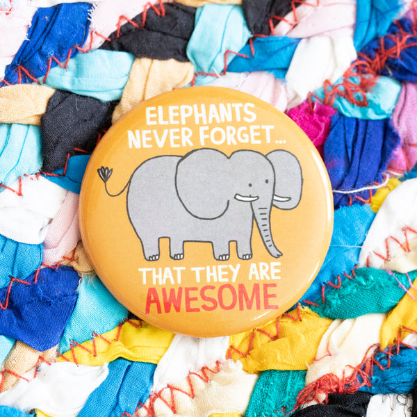 "A circular magnet. A grey elephant features, with the words ""Elephant never forget... that they are AWESOME"" are above and below. The background of the magnet is light orange."