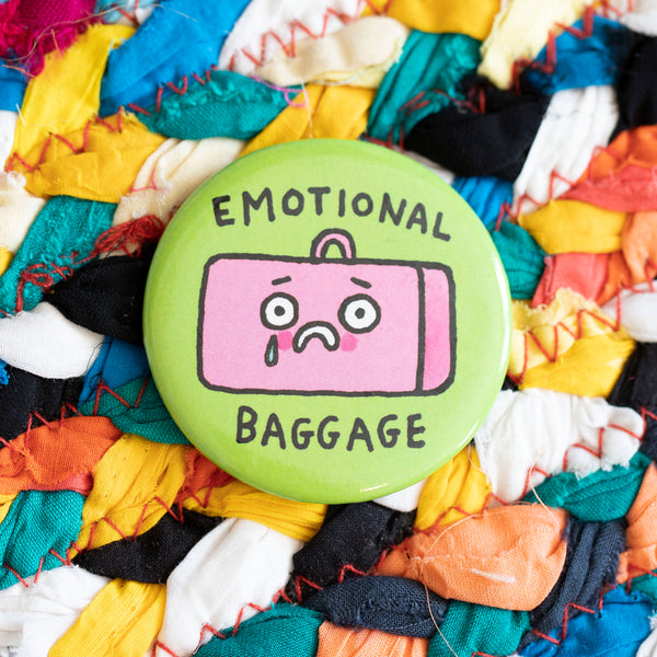 "A circular magnet. A pink suitcase looks distressed, with a tea going down it's cheek. The words ""Emotional baggage"" are above and below. The background of the magnet is green."