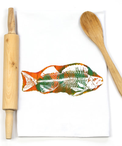 This tea towel features a print of a fish skeleton in the negative space. The paint used is orange and green against a white tea towel. A wooden rolling pin and spoon are featured purely for visual flavour.