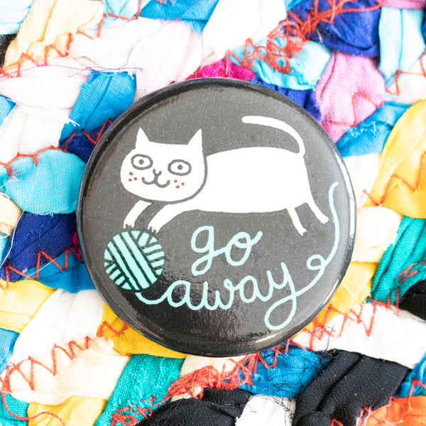 "A circular magnet. A white cat stretches over a ball of yarn. The yarn spells out the words ""go away"". The background of the magnet is black."
