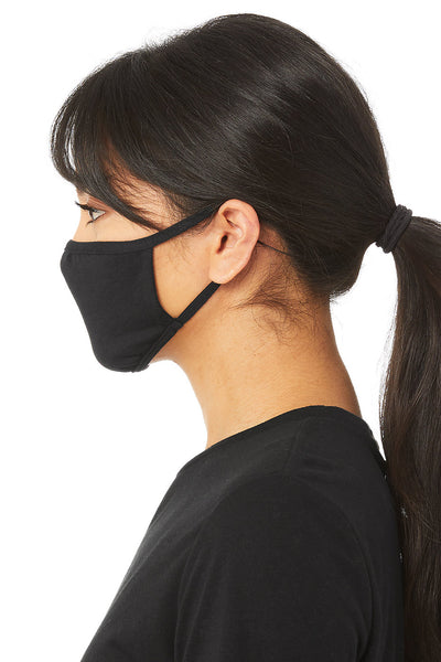 A person models this basic, black face mask. It covers their nose, mouth, and chin. This image is taken at a side angle. The mask's straps go around the person's ears.