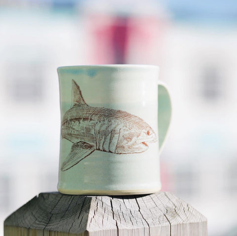 A handmade mug sitting on a fence post. It is light teal in colour with darker teal around the rim. There is a shark drawn in red wrapped around the mug, with the handle sticking out in the gap between the head and tail.
