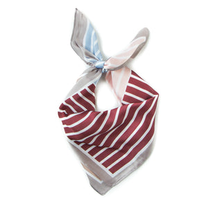 Newport Kerchief in Cranberry: a kerchief bandana with four striped sections of cranberry red, powder blue, blush pink, and caramelly tan.
