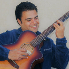 """Khalid """"Mighty Mage"""" Hussain smiling playing guitar"""