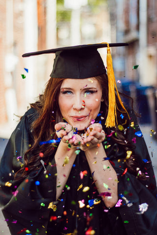 Graduate women blowing confetti