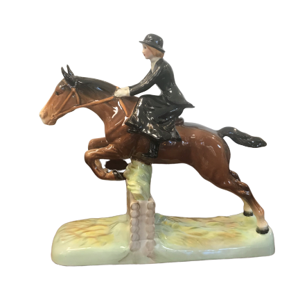 Beswick statue of lady riding a horse jumping over a hurdle