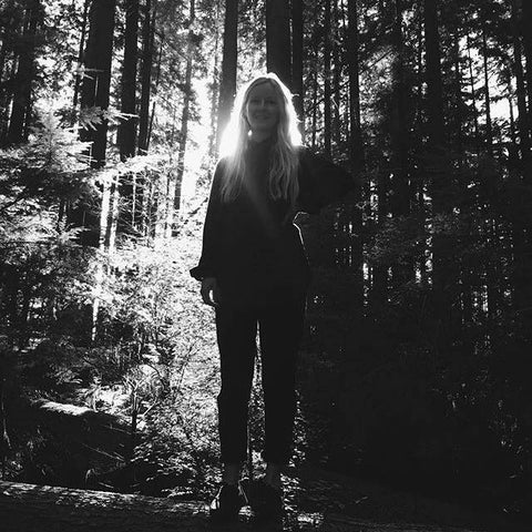 Lizz standing in the forrest with sunlight shining on her
